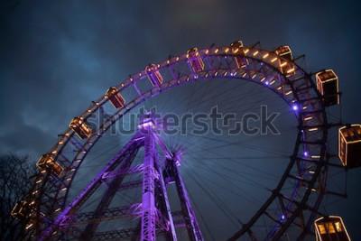 Poster Riesenrad mit Licht zwischen Wolken. London Eye. Winter. Nachthimmel und Wolken. England. Grossbritannien