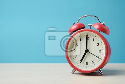 Poster Rote Weinlesealarmuhren auf Holztisch und hellblauer Hintergrundwand