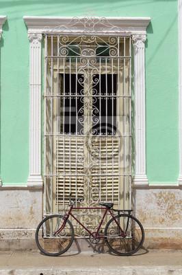 Rotes Fahrrad vor einem Haus im Kolonialstil in Trinidad, Kuba