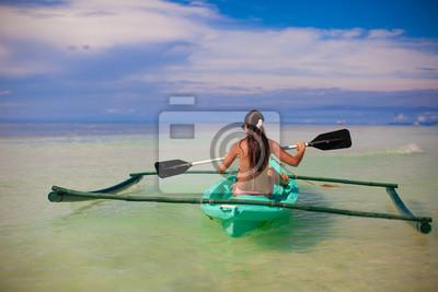 Rückansicht einer jungen Frau, Kajakfahren in der klaren Meer