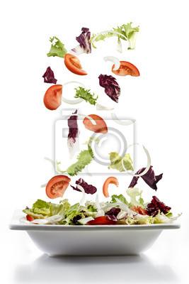Salat mit frischem Gemüse auf Teller fallen