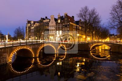 Schöne Aussicht auf den Kanälen von Amsterdam, einem UNESCO Weltkulturerbe, in den Niederlanden in der Dämmerung