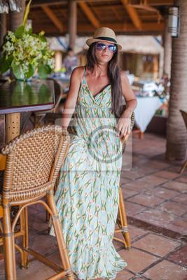 Schöne Brünette Frau im langen Kleid und Hut Entspannung in der Nähe bar