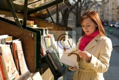 Schöne Frau in Paris Auswahl eines Buches in einem Outdoor-booksel