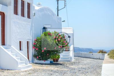 Schöne gepflasterte Straße mit alten traditionellen weißen Haus in Fira,