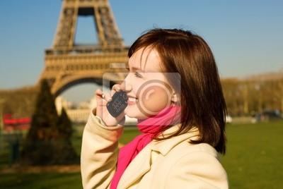 Schöne glückliche Frau mit Handy in Paris