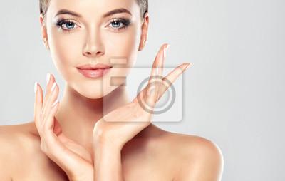 Poster Schöne junge Frau mit sauberen frischen Haut touch eigenen Gesicht. Gesichtsbehandlung . Kosmetik, Schönheit und Spa.