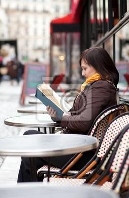 Schöne junge Mädchen liest ein Buch in Pariser Straßencafé