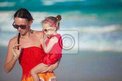 Schöne junge Mutter und ihre süße Tochter zu Fuß auf tropischen