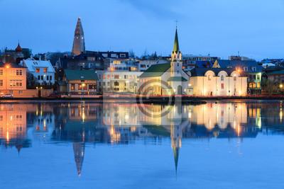 Schöne Reflexion des Stadtbildes von Reykjavik im See Tjornin an der blauen Stunde im Winter