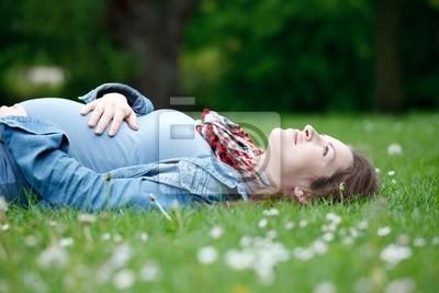 Schöne schwangere Frau entspannenden auf Gras