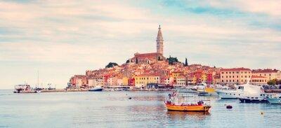 Schöne Stadtlandschaft mit Seebooten, bunten Häusern und einem alten Turm in Rovinj, Kroatien, Europa in den Pastellfarben (Ferien, Rest - Konzept)