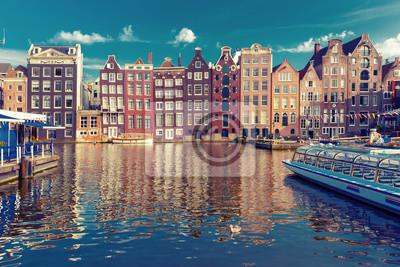 Schöne typisch niederländische Tanzhäuser am Amsterdamer Kanal Damrak im sonnigen Abend, Holland, Niederlande.