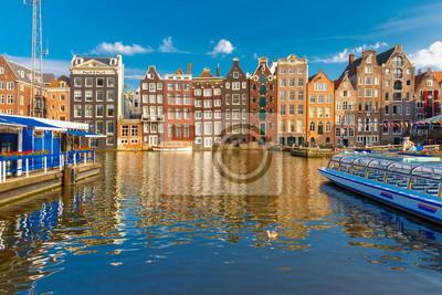Schöne typische niederländische Tanzhäuser am Amsterdamer Kanal Damrak im sonnigen Abend, Holland, Niederlande.