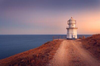 Poster Schöne weiße Leuchtturm auf der Ozean-Küste bei Sonnenuntergang. Lan