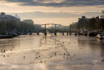 Schöne Winterpanorama des Flusses Amstel in Amsterdam, den Niederlanden, mit Blick auf die Magere Brug.