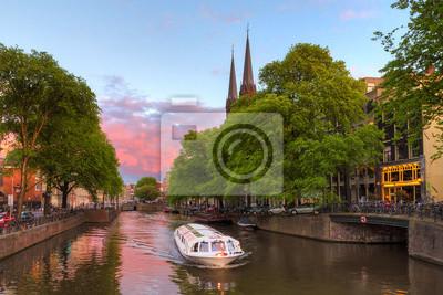 Schöner Sonnenuntergang am Singelkanal in Amsterdam mit der Krijtberger Kirche und einem Touristenboot
