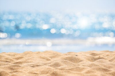 Poster Seascape abstract beach background. blur bokeh light of calm sea and sky. Focus on sand foreground.
