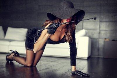 Poster Sexy Frau in Hut und Peitsche kniend auf dem Boden drinnen