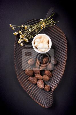 Shea Butter und Shea Butter Nüsse auf schwarzem Hintergrund