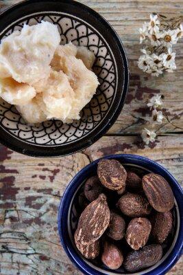Shea-Nüsse und Sheabutter auf einer hölzernen Oberseite