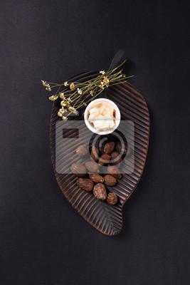 Sheabutter und Sheabutter Nüsse auf schwarzem Hintergrund
