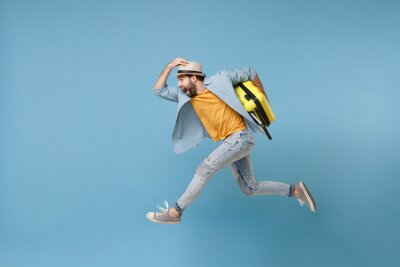 Poster Side view of excited traveler tourist man in yellow clothes isolated on blue background. Male passenger traveling abroad on weekends. Air flight journey concept. Jumping like running, hold suitcase.