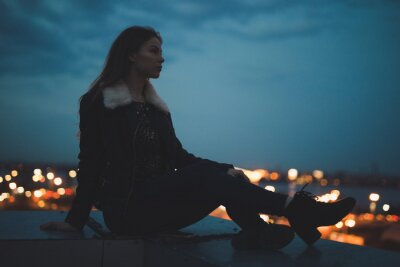 Poster Silhouette of alone woman sitting on the roof, city on background