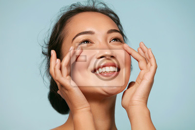 Poster Skin care. Woman with beauty face touching healthy facial skin portrait. Beautiful smiling asian girl model with natural makeup touching glowing hydrated skin on blue background closeup