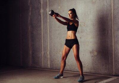 Poster Slim attraktive Sportlerin in einem Kettlebell Training