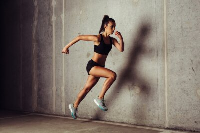 Poster Slim attraktive Sportlerin läuft gegen einen konkreten Hintergrund