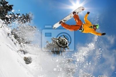 Snowboarder springend gegen blauen Himmel