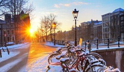 Sonnenaufgang über den Kanal Straßen von Amsterdam, den Niederlanden, mit Fahrrädern im Schnee an einem schönen Wintertag. HDR