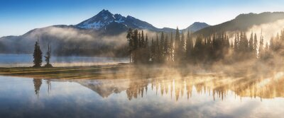 Poster South Sister and Broken Top reflect over the calm waters of Sparks Lake at sunrise in the Cascades Range in Central Oregon, USA in an early morning light. Morning mist rises from lake into trees.