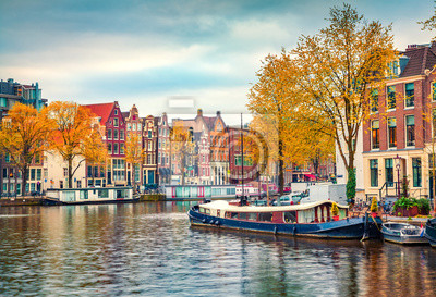 Splendid autumn scene of Amsterdam city. Famous Dutch channels and great cityscape. Colorful morning landscape in Netherlands, Europe. Traveling concept background..