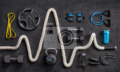Poster Sports equipment on a black background. Top view. Motivation