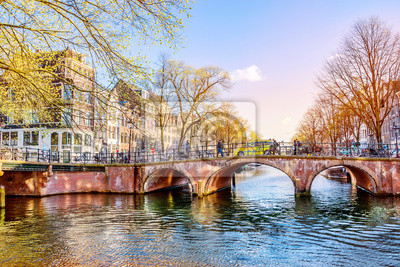 Stone arched bridge over Amsterdam canal in spring sunny evening, Netherlands