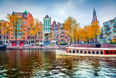 Stunning autumn cityscape of Amsterdam. Famous Dutch channels and excursion boat. Colorful morning landscape in Netherlands, Europe. Traveling concept background..