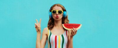 Poster Summer fashion portrait of young woman in headphones listening to music with juicy slice of watermelon, female model blowing her lips posing on a colorful blue background