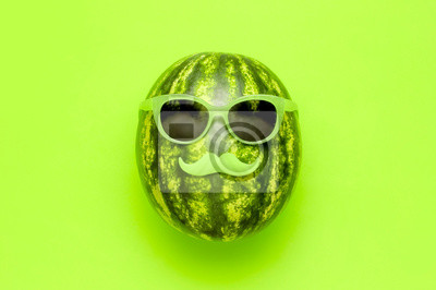 Poster Summer funny watermelon in green glasses and with green mustache on bright green background top view flat lay. Minimal fruit concept. Creative product idea, summer festival, summer background