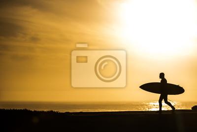Surfer in a beautiful golden sunset in Santa Cruz