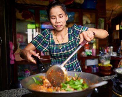 Poster thai woman cooking traditional red curry in wok