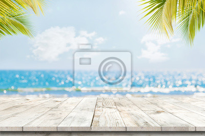 Poster Top of wood table with seascape and palm leaves, blur bokeh light of calm sea and sky at tropical beach background. Empty ready for your product display montage.  summer vacation background concept.