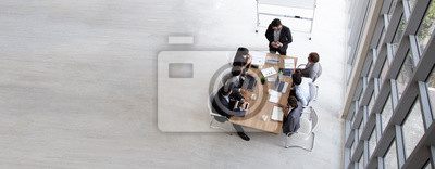 Poster Top view of group of multiethnic busy people working in an office, Aerial view with businessman and businesswoman sitting around a conference table with blank copy space, Business meeting concept