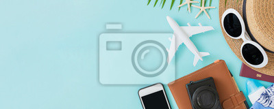 Poster Top view of traveler accessories, tropical palm leaf and airplane on blue background with empty space for text. Travel summer holiday vacation banner concept.