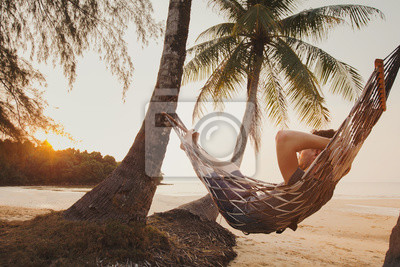 Poster tourist relaxing in hammock on tropical beach with coconut palm trees, relaxation and leisure tourism
