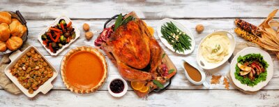 Poster Traditional Thanksgiving turkey dinner. Above view table scene on a rustic white wood banner background. Turkey, mashed potatoes, stuffing, pumpkin pie and sides.