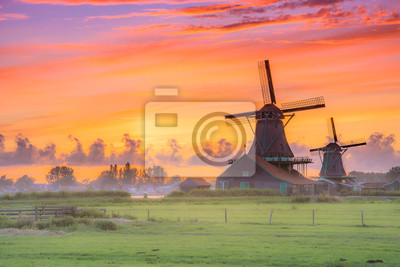 Poster Traditional village with dutch windmills and river at sunset, Holland, Netherlands.