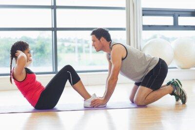 Poster Trainer helfen Frau tun Bauch-Crunches im Fitness-Studio