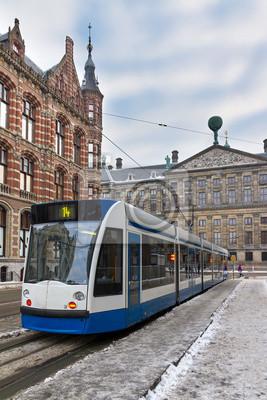 Tram in Amsterdam, den Niederlanden, mit dem Magna Plaza und den Königspalast im Winter
